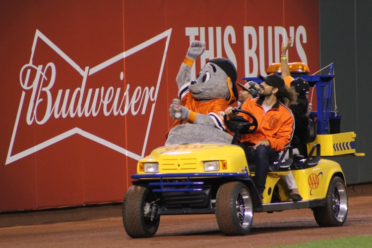 Lou Seal takes a couple of birthday gals for a ride, tossing goodies into the stands for fans